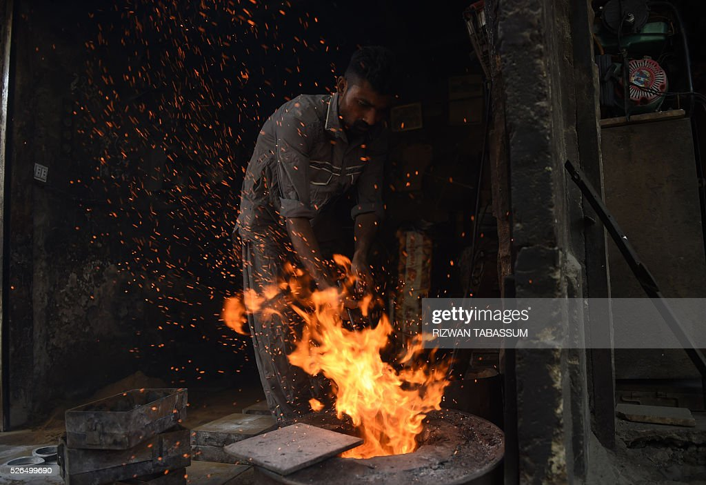 A Pakistani labourer works in an iron factory in Karachi on April 30,2016, on the eve of International Labour Day. / AFP / RIZWAN