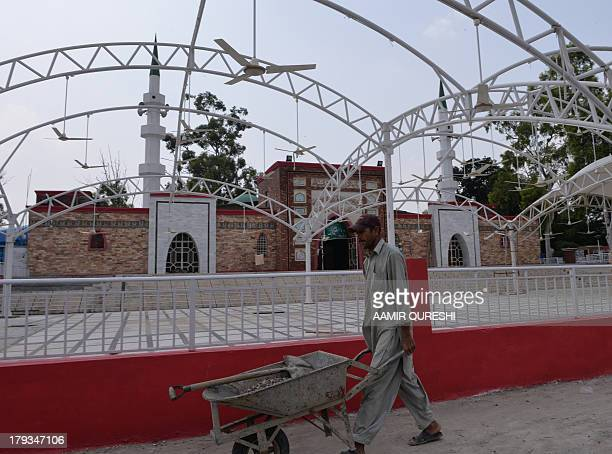 A Pakistani labourer works outside the Red Mosque in Islamabad on September 2 2013 Pakistan police registered murder charges against former military...