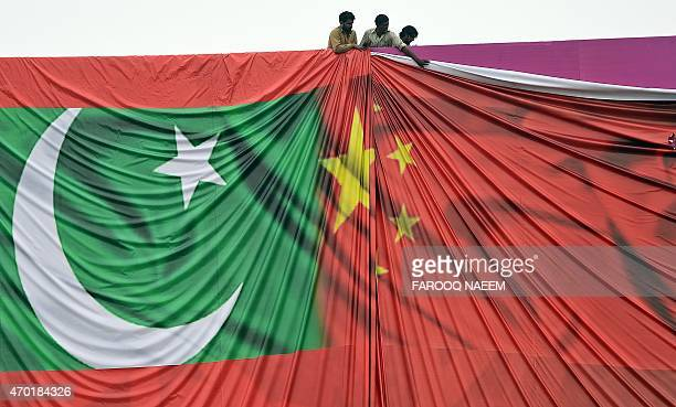 Pakistani labourers arrange a welcome billboard featuring the Chinese and Pakistani national flags ahead of the forthcoming visit by Chinese...
