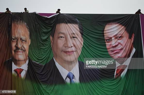 Pakistani labourers arrange a welcoming billboard featuring pictures of visiting Chinese President Xi Jinping and his Pakistani counterpart Mamnoon...