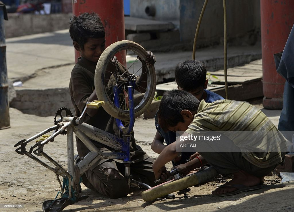 Pakistani labourers dismantle a bicycle at a shop in Lahore on May 31, 2016. Some 45 percent of Pakistan's population of 182 million is aged below 22. / AFP / ARIF ALI
