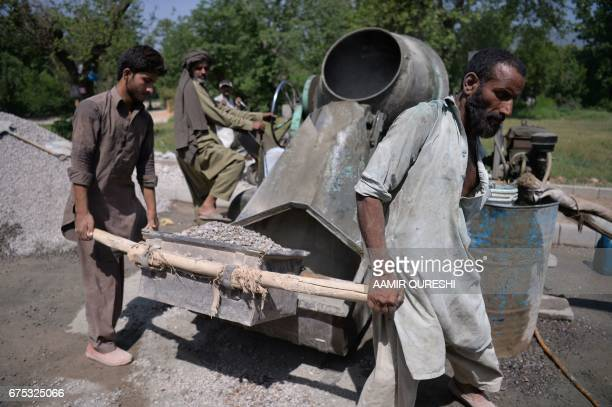 Pakistani labourers fill gravel in a mixer to prepare concrete in Islamabad on May 1 on International Labour Day or May Day / AFP PHOTO / AAMIR...