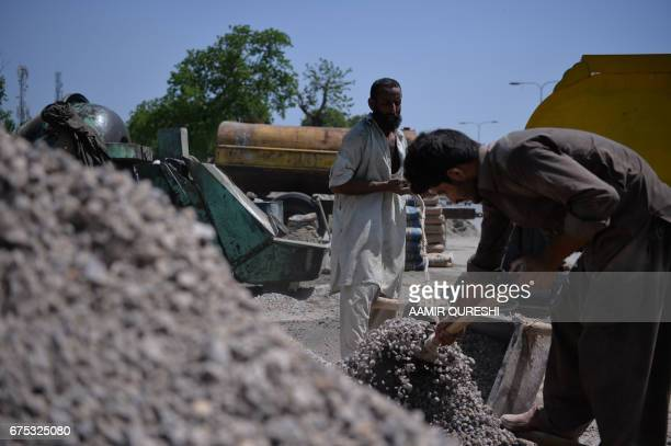 Pakistani labourers fill gravel to prepare concrete near a mixer in Islamabad on May 1 on International Labour Day or May Day / AFP PHOTO / AAMIR...