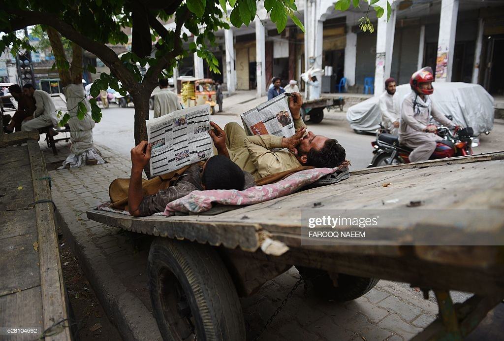 Pakistani labourers read newspapers as they rest on a cart at a market in Rawalpindi on May 4, 2016. / AFP / FAROOQ