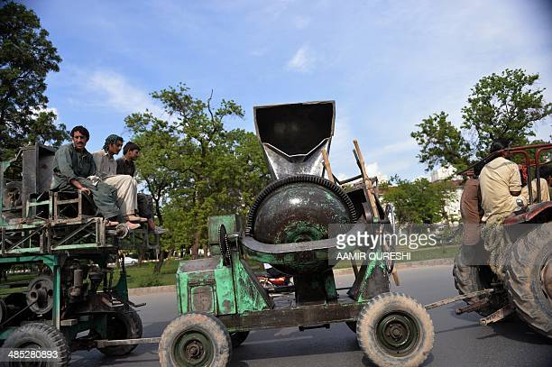 Pakistani labourers travel with a concrete mixer on a street in Islamabad on April 17 2014 Government statistics estimate the literacy rate at 58...