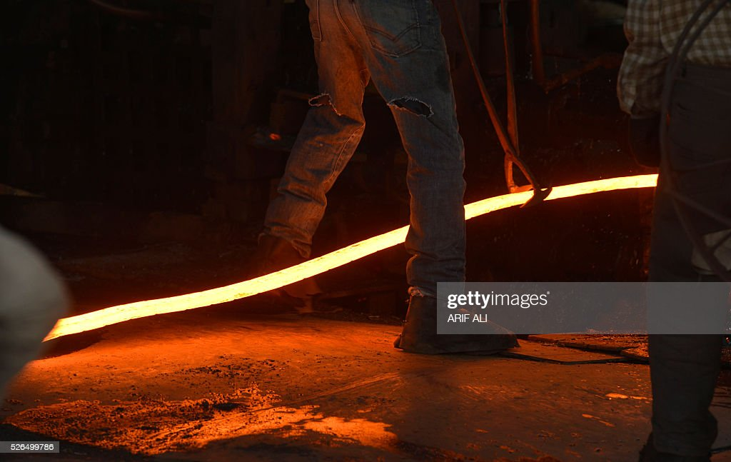 Pakistani labourers work in an iron factory in Lahore on April 30, 2016, on the eve of International Labour Day. / AFP / ARIF ALI