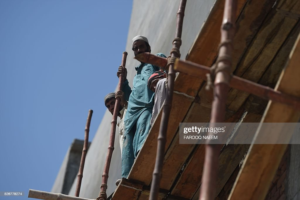 Pakistani labourers work on a construction site in Islamabad on May 1, 2016, on International May Day. International Labour Day is marked annually on May 1. / AFP / FAROOQ