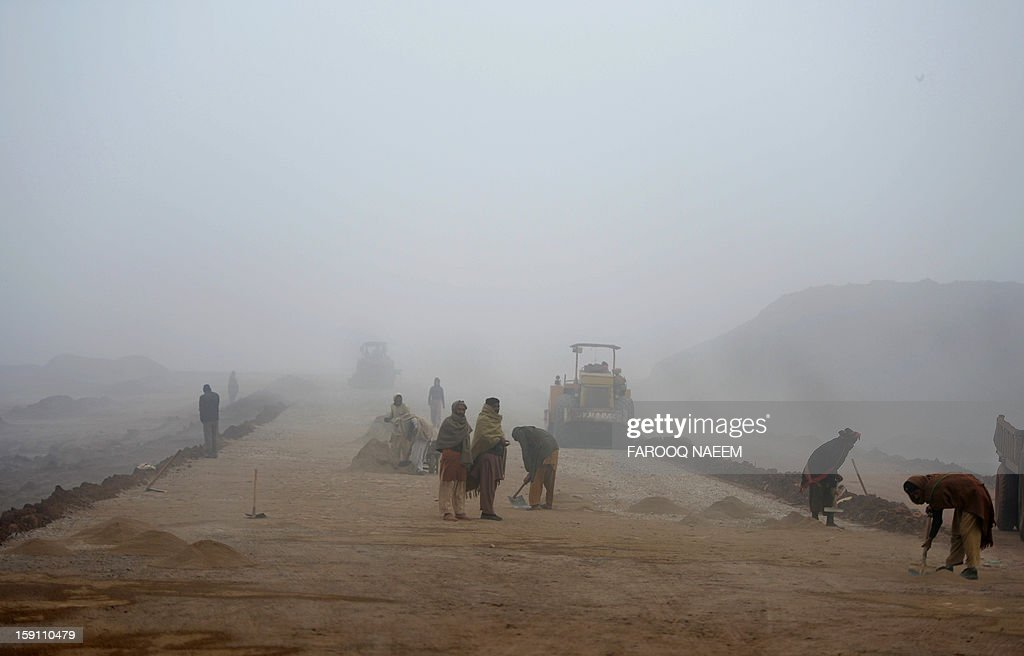 Pakistani labourers work on an under-construction road during a foggy morning in Islamabad on January 8, 2012. The fog has also disrupted flight schedules at the Islamabad airport and four Islamabad-bound flights from Dubai and Afghanistan were diverted to Lahore. AFP PHOTO/Farooq NAEEM