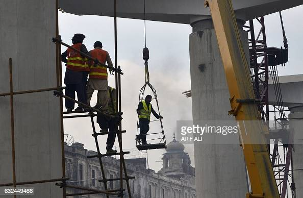 Pakistani labourers work to build a concrete pillar for train tracks in Lahore on January 23 2017 In the 2015/2016 fiscal year the economy grew 47...