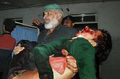 A Pakistani man carries an injured student at a hospital following an attack by Taliban gunmen on a school in Peshawar on December 16 2014 Taliban...