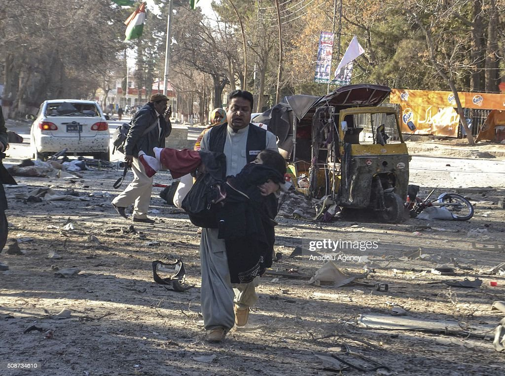 A Pakistani man carries an injured victim at the site of a suicide attack in Quetta, Pakistan, on February 6, 2016. At least nine people were killed and several others wounded in the suicide attack near the premises of the heavily guarded Quetta district courts on Saturday.