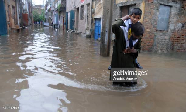 Pakistani man carries his child to school as he wades through a flooded street on September 5 2014 in Rawalpindi Pakistan Due to the heavy monsoon...