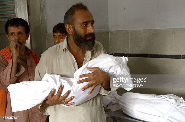 A Pakistani man carries the body of his three year old son outside the cold storage of the Edhi morgue in Karachi on June 22 after his death in a...