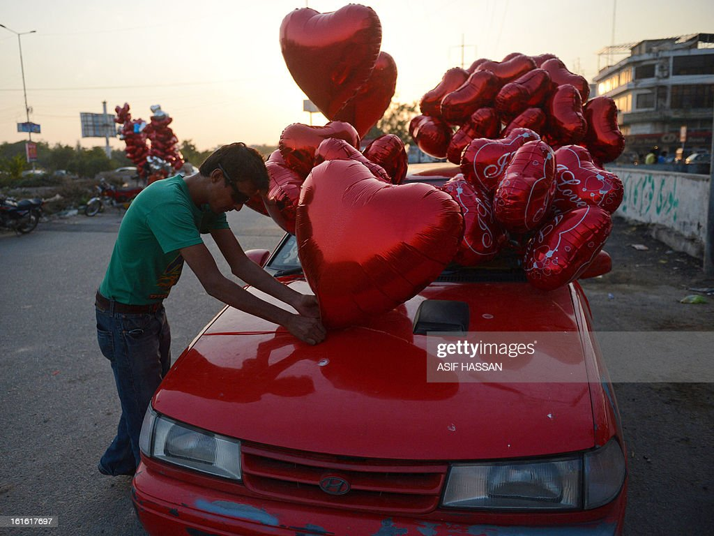 A Pakistani man displays heart-shaped balloons on his car ahead of Valentine's Day in Karachi on February 13, 2013. Valentine's Day is increasingly popular among younger Pakistanis, many of whom have taken up the custom of giving cards, chocolates and gifts to their sweethearts to celebrate the occasion. AFP PHOTO/Asif HASSAN