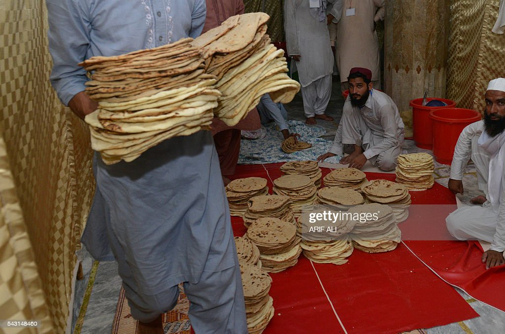 A Pakistani man distributes bread to Muslims before breaking their fast on the start of Itikaf in a mosque in Lahore on June 26, 2016. Itikaf is a spiritual retreat in a mosque for men, usually held during the last 10 days of Ramadan and during which Muslims spend the evening and night in the mosque devoting their time to solitary prayers and reading the Koran. / AFP / ARIF ALI