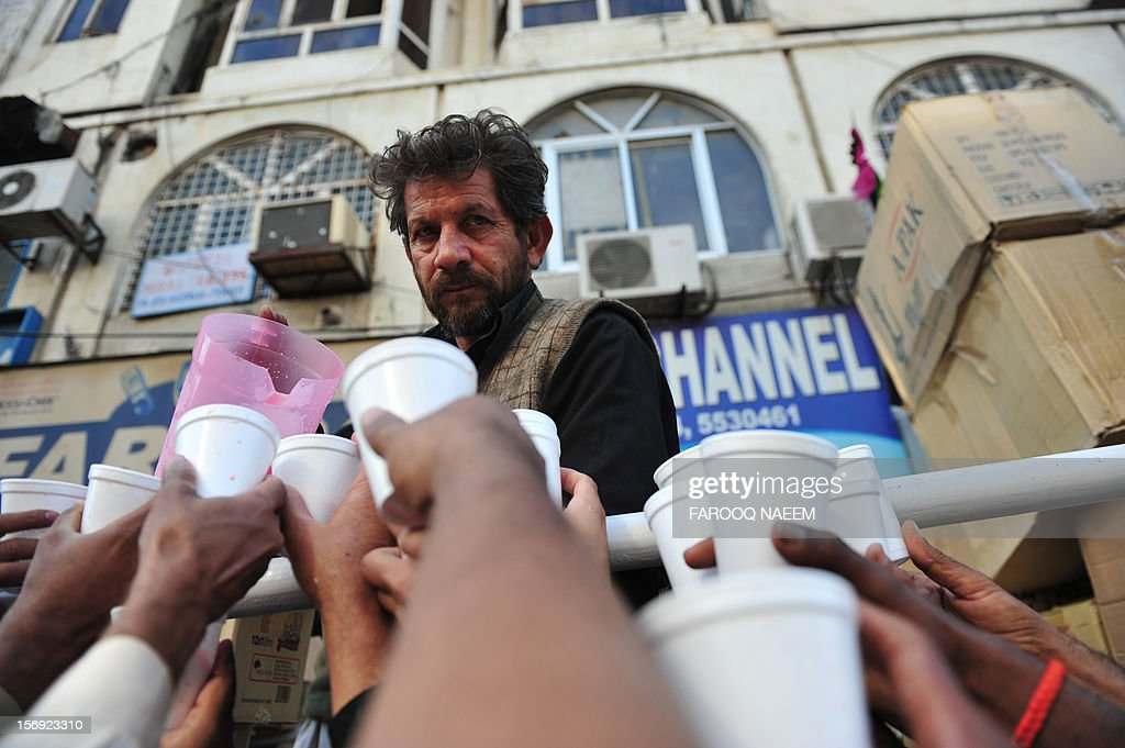A Pakistani man distributes drinks to Shiite Muslims during a religious procession in Rawalpindi on November 25, 2012. A bomb attack on a Shiite Muslim procession killed five mourners and wounded more than 80 in northwest Pakistan on November 25 as Shiites marked their holiest day Ashura, officials said.