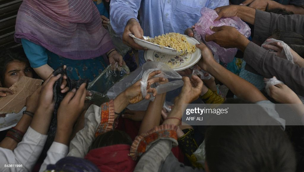 A Pakistani man distributes food during the month of Ramadan in Lahore on June 29, 2016. Throughout the month, devout Muslims must abstain from food, drink and sex from dawn until sunset when they break the fast with the Iftar meal. / AFP / ARIF ALI