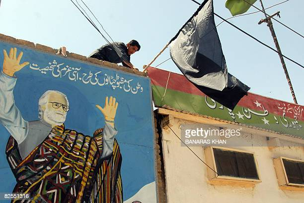 A Pakistani man installs a black flag on the top of picture of late tribal chieftain Nawab Akbar Bugti in Quetta on August 26 2008 on the second...