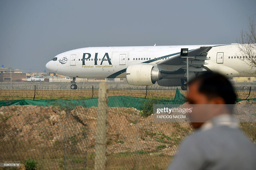 A Pakistani man looks on as a Pakistan International Airline (PIA) plane taxis on the runway on the way to Saudi Arabia during the PIA employees strike in Islamabad on February 8, 2016. The strike continued despite Prime Minister Nawaz Sharif's warning that the demonstration was illegal and those taking part could face up to a year in prison under a law that restricts union activity in state-administered sectors. AFP PHOTO / Farooq NAEEM / AFP / FAROOQ NAEEM