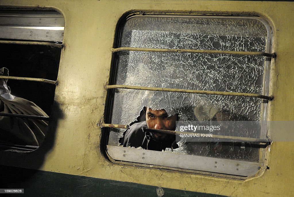 A Pakistani man looks through a broken mirror on the Jaffar Express train after an attack at a railway station in Quetta on early 6, 2012. Unidentified gunmen fired at a train in Pakistan's restive Baluchistan province, killing at least five people and seriously injuring 20 others. AFP PHOTO/Banaras KHAN