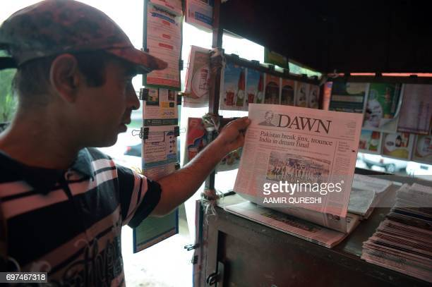A Pakistani man picks up a morning newspaper with front page coverage of Pakistan's victory against India in the ICC Champions Trophy final cricket...