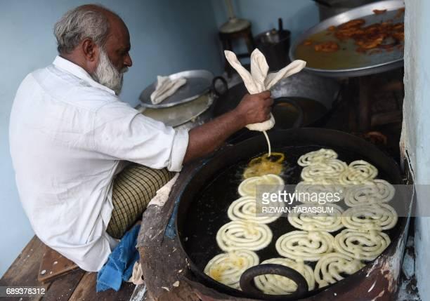 A Pakistani man prepares jalebi sweet as part of the holy month of Ramadan on May 28 2017 in Rawalpindi The world's nearly 15 billion Muslims on May...