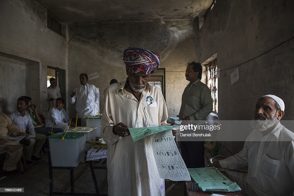 A Pakistani man receives his ballot paper before casting his vote at a polling station on May 11, 2013 on the outskirts of Lahore, Pakistan. Millions of Pakistanis cast their votes in parliamentary elections; the first time in the country's history that an elected government will hand over power to another elected government.