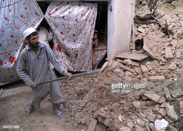 A Pakistani man removes debris after an earthquake in Kohat on October 26 2015 A powerful 75 magnitude earthquake killed at least 70 people as it...