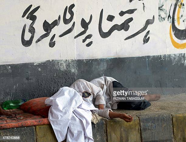 A Pakistani man rests next to a street during a heatwave in Karachi on June 24 2015 A deadly heatwave that has killed nearly 700 people in southern...