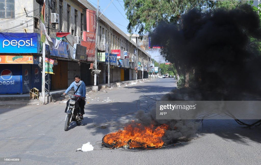 A Pakistani man rides past burning tyres set on fire by protesters demonstrating against Imran Khan in Hyderabad on May 19, 2013. Khan May 19, blamed a rival political leader for the killing of a senior member of his party, who was gunned down outside her home in the violence-plagued city of Karachi on the eve of a partial re-run in the southern city of the May 11 election. AFP PHOTO/ Yousuf NAGORI