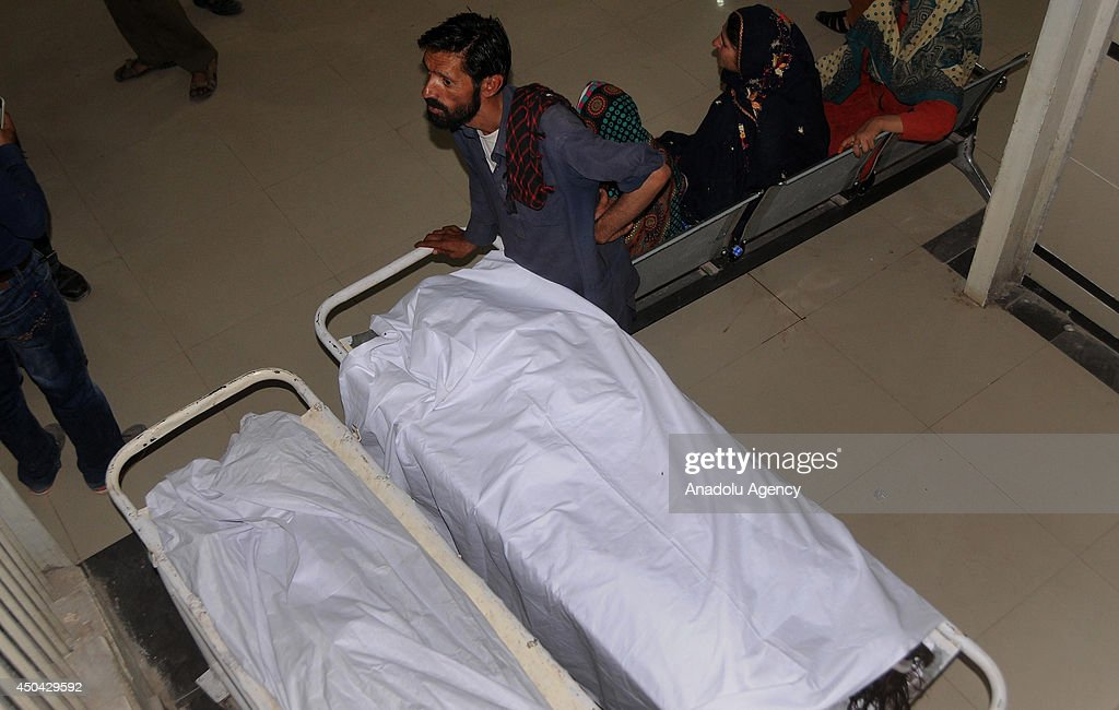 A Pakistani man stands next to the bodies of the children died when roof of a house collapsed in Rawalpindi on June 11, 2014. At least five children died and three were injured when a house in Dhoke Lalyal area of Rawalpindi collapsed while they were asleep inside. The injured were shifted to hospital for medical treatment.