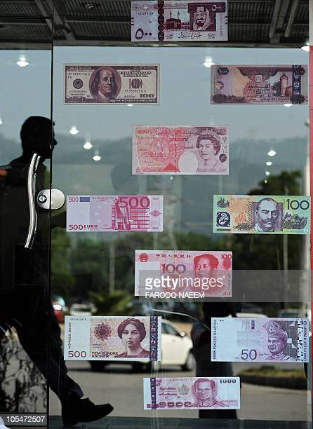 A Pakistani man walks past a currency exchange shop with various notes displayed in the window in Islamabad on October 14 2010 The US dollar fell...