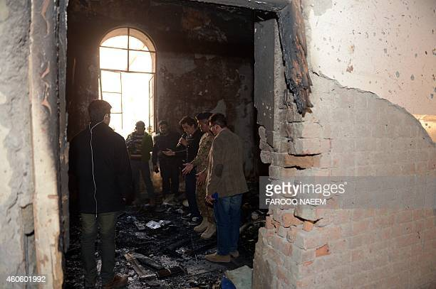 Pakistani media and soldiers look the burnt room at an armyrun school a day after an attack by Taliban militants in Peshawar on December 17 2014...