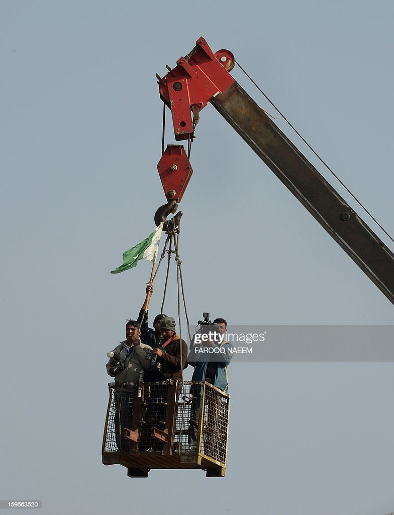 Pakistani media representatives take photographs and video from a crane as supporters of Pakistan cleric Tahir-ul Qadri participate on the third day of a protest rally in Islamabad on January 16, 2013. Pakistani protesters rallied for a third day January 16 in the largest political demonstration seen for years in the capital, calling on the government to quit after the Supreme Court ordered the arrest of the prime minister. AFP PHOTO/Farooq NAEEM
