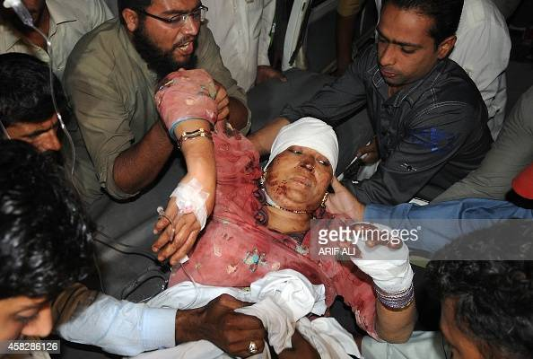 Pakistani men carry a wounded woman at a hospital in Lahore after a suicide bomb attack near the Wagah border gate on November 2 2014 A suicide...