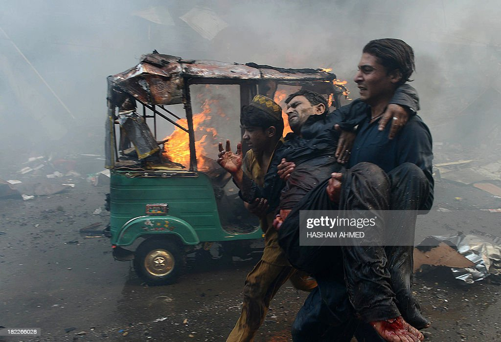 Pakistani men carry an injured blast victim at the site of a bomb explosion in the busy Kissa Khwani market in Peshawar on September 29, 2013. A bomb explosion killed at least 31 people in Pakistan's northwestern city of Peshawar, officials said -- the third deadly strike to hit the city in the last week.