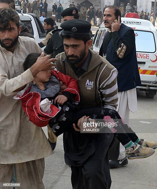 Pakistani men carry an injured school girl to a hospital following an attack by Taliban gunmen on a school in Peshawar on December 16 2014 At least...