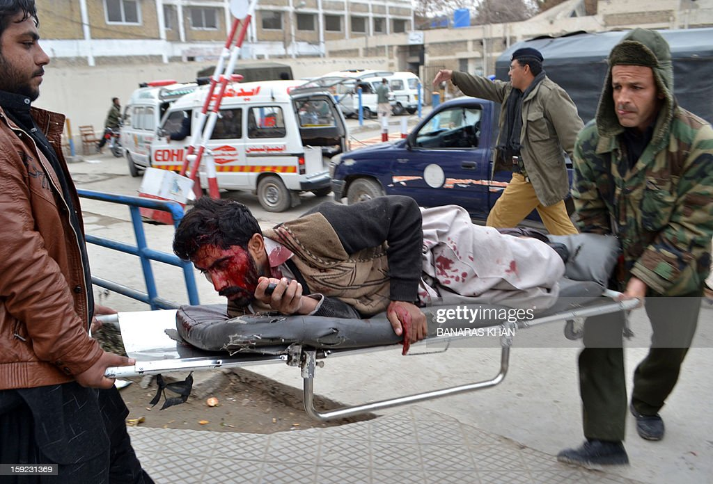 Pakistani men carry in an injured blast victim to a hospital after a bomb explosion in Quetta on January 10, 2013. A bomb attack killed 11 people and wounded dozens more in a crowded part of Pakistan's southwestern city of Quetta, police said. AFP PHOTO/Banaras KHAN
