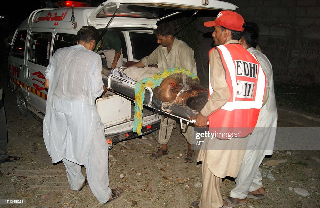 Pakistani men carry the body of a blast victim at the site of suicide car bombing in the southern city of Sukkur on July 24, 2013. Suicide car bombers and gunmen attacked a government complex housing offices of Pakistan's top intelligence agency, sparking a shootout that killed seven people, officials said. AFP PHOTO / SHAHID ALI