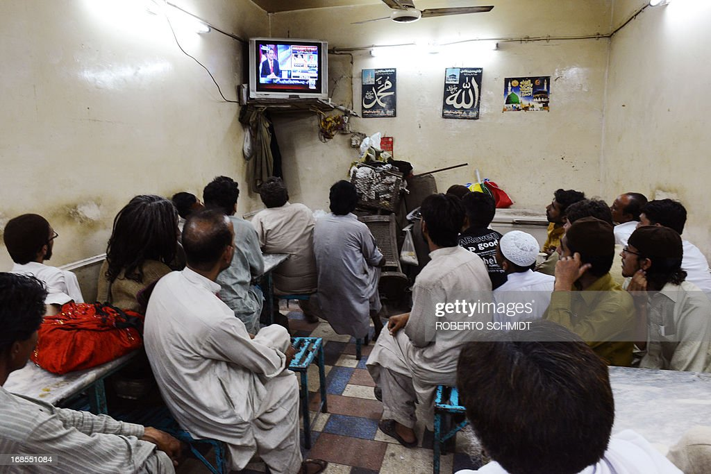 Pakistani men crowd a small tea hall as they watch live news reports of incoming elections results after the polls closed in Lahore on May 11, 2013. Counting got underway Saturday in Pakistan's landmark elections after millions of people defied deadly Taliban attacks to take part in an historic democratic transition in the nuclear-armed state. AFP PHOTOS/Roberto SCHMIDT