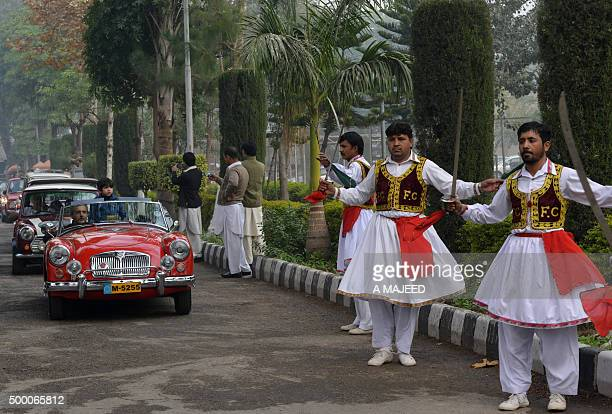 Pakistani men drive vintage cars at a classic car show next to men in traditional attire in Peshawar on December 5 2015 The Annual Classic Car Show...