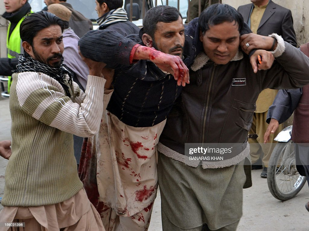 Pakistani men help an injured blast victim to a hospital after a bomb explosion in Quetta on January 10, 2013. A bomb attack killed 11 people and wounded dozens more in a crowded part of Pakistan's southwestern city of Quetta, police said. AFP PHOTO/Banaras KHAN
