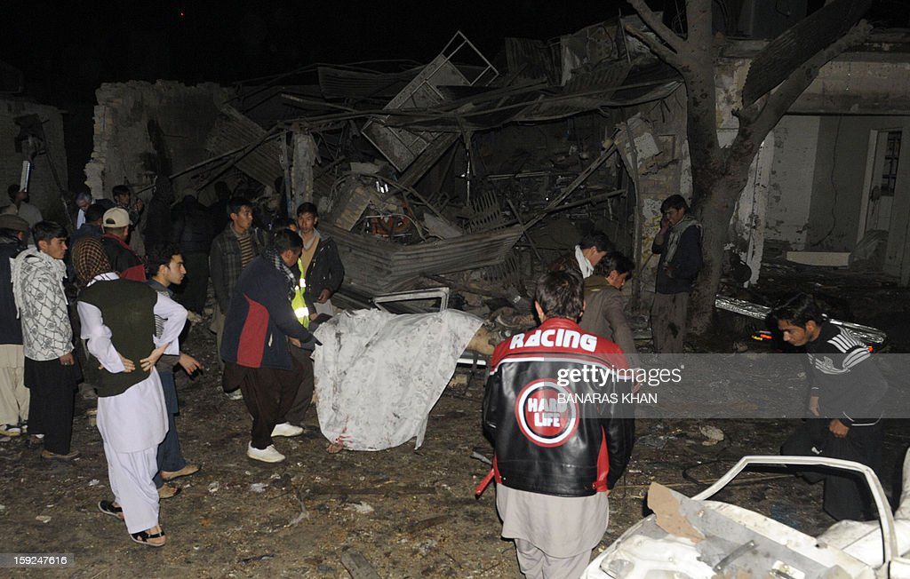 Pakistani men remove a dead body from the site of a bomb attack in Quetta on January 10, 2013. At least 10 people were killed as two successive bombs exploded outside a snooker club in the southwestern city of Quetta late, hours after a separate blast left 11 dead, police said.