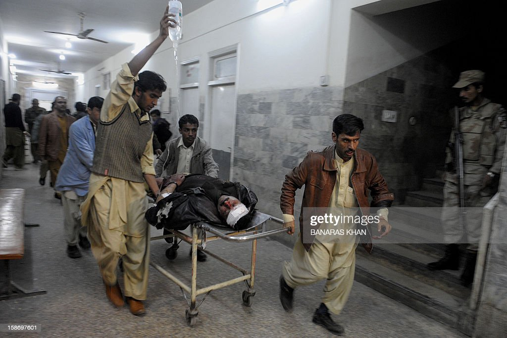 Pakistani men shift an injured policeman into a hospital after unidentified gunmen attacked a check point in Quetta on December 24, 2012. Gunmen shot dead two policemen and injured another at a check point in Pakistan's troubled southwestern city of Quetta today, police said. Hundreds of people have died since Baluch rebels rose up in 2004 demanding political autonomy and a greater share of profits from the region's riches, including natural oil, gas and mineral resources. AFP PHOTO / Banaras KHAN