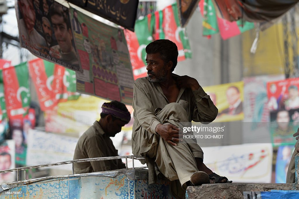 Pakistani men sit surrounded by political propangda banners on a street corner in the old city in Lahore on May 10, 2013, one day before some 86 million registered voters will go to the polls to elect lawmakers to the lower house of parliament and four provincial assemblies. Pakistan's general elections will mark the first democratic transition of power in the country's 66-year existence. AFP PHOTOS/Roberto SCHMIDT