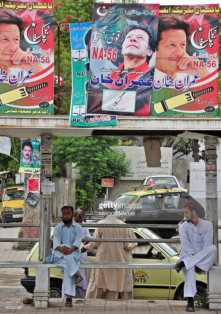 Pakistani men sit under the electoral posters on a bus stop in Rawalpindi on April 26, 2013. May 11 national polls should see power pass from a civilian government that has served a full term to another through the ballot box for the first time in the nuclear-armed country's turbulent history. AFP PHOTO/Farooq NAEEM
