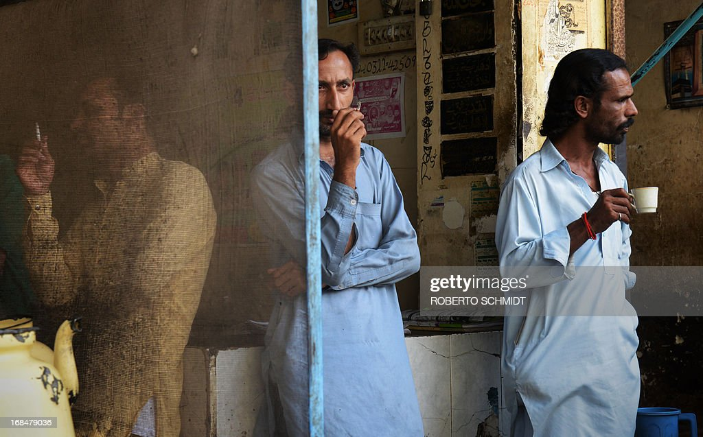 Pakistani men stand outside a shop to drink Chai or tea on a street corner in the old city in Lahore on May 10, 2013, one day before some 86 million registered voters will go to the polls to elect lawmakers to the lower house of parliament and four provincial assemblies. Pakistan's general elections will mark the first democratic transition of power in the country's 66-year existence. AFP PHOTOS/Roberto SCHMIDT