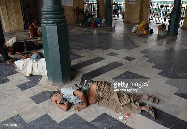 Pakistani men take rest on the floor of a railway platform during a hot day in Karachi Pakistan on June 22 2015 Nearly 200 people have died in a...