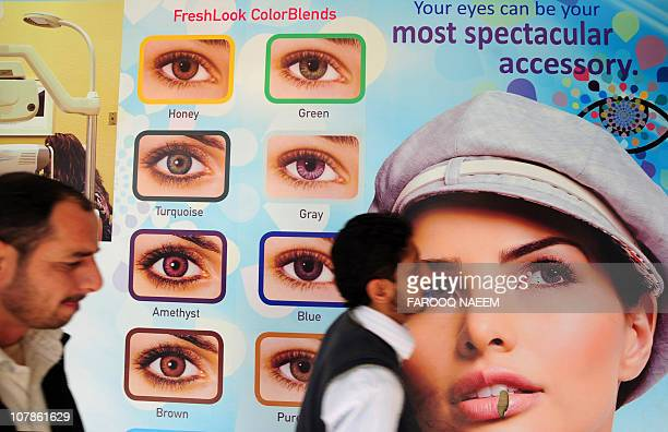 Pakistani men walk past an advertisement for eye contact lenses in the commercial area of Islamabad on December 28 2010 AFP PHOTO/Farooq NAEEM