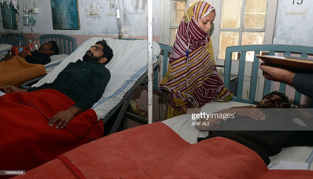 Pakistani men who fell ill after drinking a toxic cough syrup rest at a hospital in Lahore on November 26, 2012. At least 16 people have died after drinking a toxic cough syrup in the Pakistani city of Lahore, forcing authorities to close three pharmacies and a medicine factory, officials said. AFP PHOTO/Arif ALI